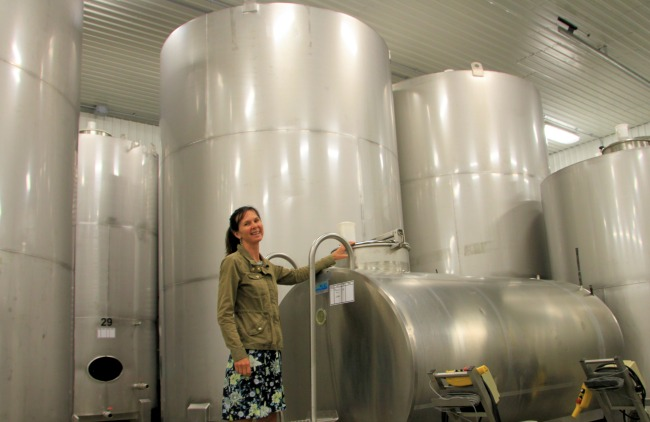 Catherine Langlois with her first wine tank anud a forest of massive steel tanks